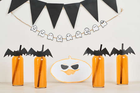 Garlands, drawing of pumpkin and decorated bottles with fizzy cocktail at Halloween celebration