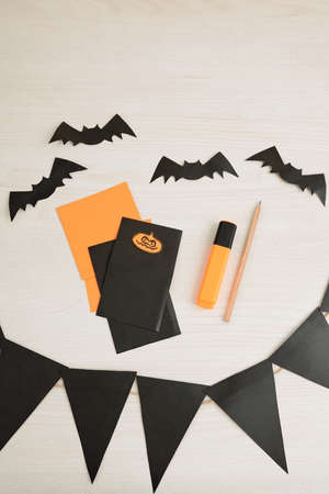 Halloween garland, paper bats and party invitations on table, view from above