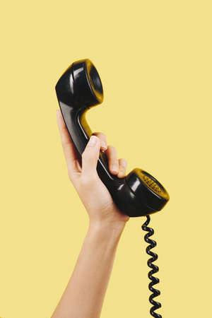Hand of person holding black telephone receiver