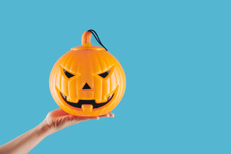 Hand of person holding plastic spooky jack-o-latern lamp for Halloween celebration, isolated on light blue Stock Photo
