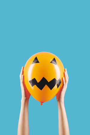 Person holding balloon with scary face for Halloween celebration with both hands, isolated on blue