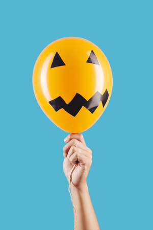 Scary face reminding jack-o-lantern on orange balloon in hand of person, isolated on light blue