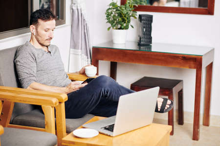 Young man enjoying cup of coffee and scrolling social media on smartphone after working on laptop at home