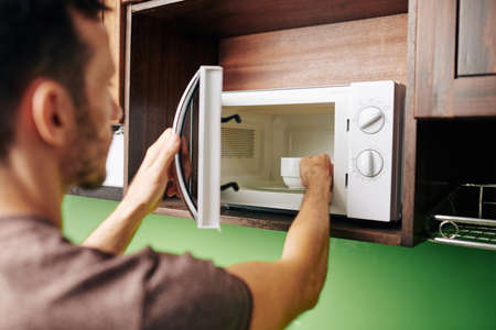Man putting bowl of soup in microwave to heat it for the dinner