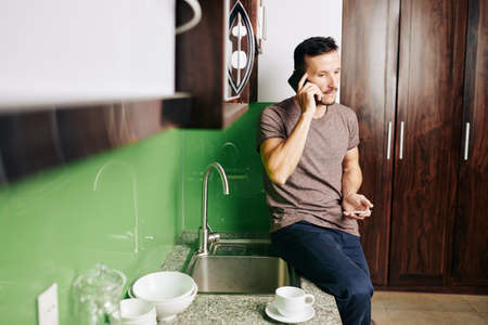 Handsome young man sitting on kitchen counter, talking on phone and ordering pizza and drinks
