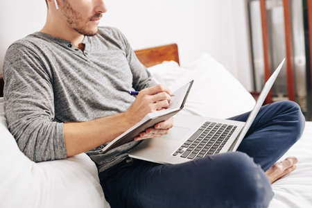 Cropped image of man wearing earbuds when watching webinar on laptop and taking notes in planner Imagens