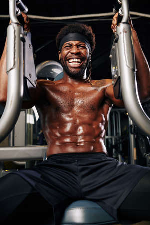 Shirtless cheerful muscular man training in gym machine and doing upper body exercise Stok Fotoğraf - 131068714