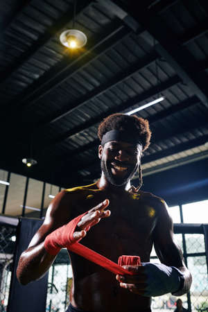 Smiling Black Muay Thai boxer wrapping wrists with bandage to protect them during training session 스톡 콘텐츠