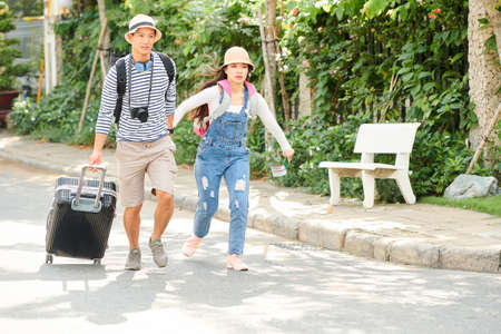 Young Vietnamese couple with big suitcase holding hands when hurrying to bus station