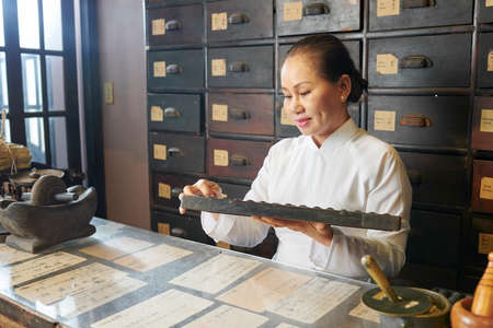 Mature Vietnamese woman working at old traditional apothecary and counting on abacus