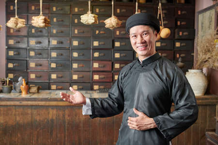Happy Asian man making welcoming gesture and inviting customers to traditional Chinese pharmacy
