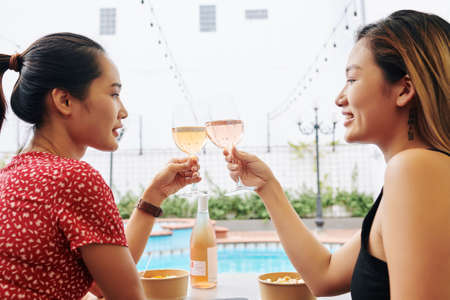 Beautiful young Vietnamese women resting by swimming pool and toasting with wine glasses when enjoying vacation