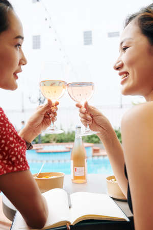Pretty happy Asian female friends sitting by swimming pool and enjoying good wine and conversation Banco de Imagens
