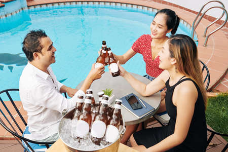 Group of happy Asian people sitting at table by swimming pool and clinking beer bottles