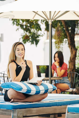 Pretty young Asian woman sitting on chaise-lounge with pillow on her laps and writing in planner