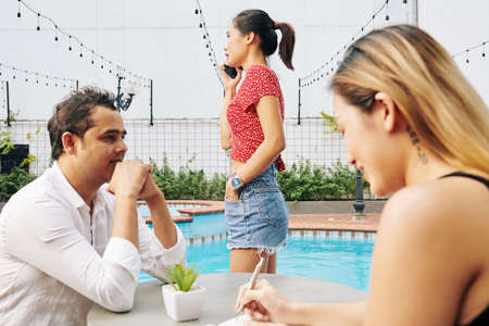 Digital nomads working by swimming pool: colleagues discussing work and young woman calling budinrdd partner or client