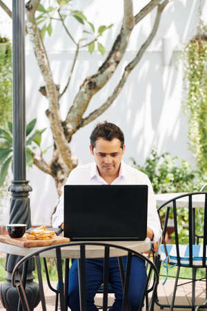 Young Indian software engineer eating breakfast in outdoor cafe and checking e-mails on laptop screen