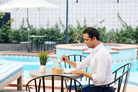 Indian entrepreneur enjoying healthy breakfast and checking planner when sitting at table by swimming pool