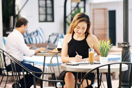 Beautiful young Vietnamese business lady drinking iced coffee and writing down plans in diary 스톡 콘텐츠 - 131947334