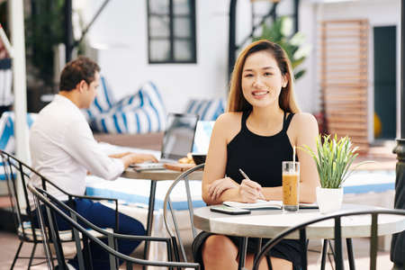 Portrait of young beautiful Asian businesswoman sitting at cafe table with glass of iced coffee and writing down her thoughts