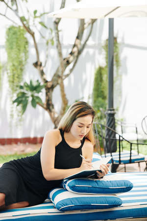 Creative young Asian businesswoman resting on striped chaise-lounge and taking notes in journal