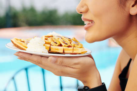 Cropped image of young smiling woman smelling fresh tasty Belgian waffles with caramel topping