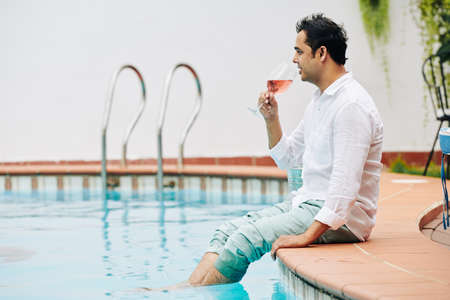 Pensive Indian man in jeans and white shirt sitting on edge of swimming pool and enjoying glass of tasty cold rose wine 版權商用圖片