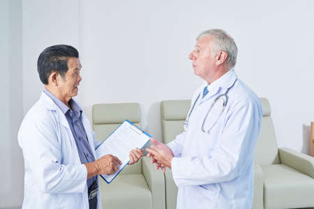 Senior multi-ethnic general practitioners in white lab coats talking in hall of medical clinic