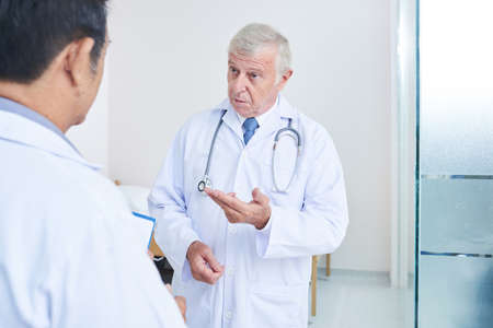 Aged doctor with stethoscope talking to his colleague and helping his to define diagnosis