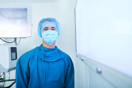 Portrait of positive young Vietnamese intern surgeon in scrubs, protective msak and cap standing in operating room