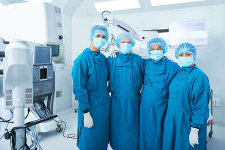 Hugging surgical team in scrubs standing in operating theater after surgery and looking at camera