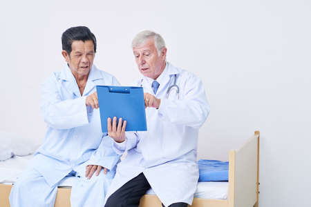 Experienced doctor and his senior patient discussing complaints and tests results in medical history Zdjęcie Seryjne