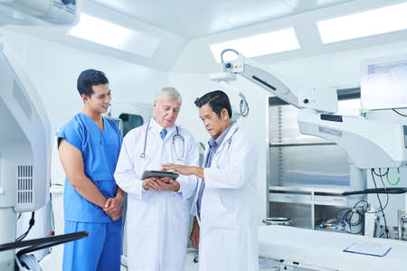 Physicians and surgeon meeting in operating theater to discuss medical history of patient befor surgery Zdjęcie Seryjne
