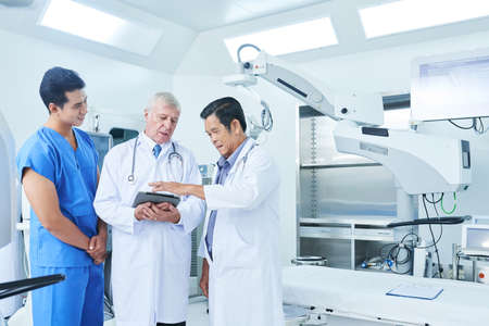 Multi-ethnic general practitioners and surgeon discussing patients data on the screen of tablet computer in operating theatre