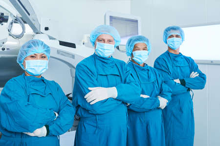 Confident positive surgical team in uniform standing in operating room with their arms folded and looking at camera