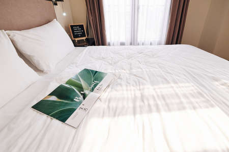 Opened magazine on queen bed in empty hotel room prepared for new guests