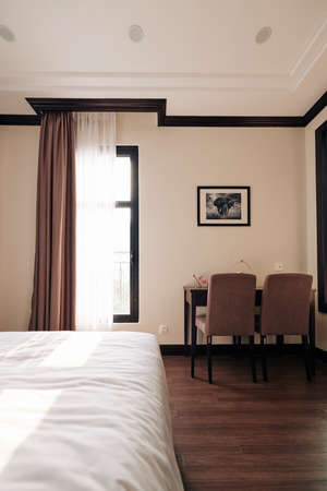 Empty spa resort room with queen bed, small table and two chairs