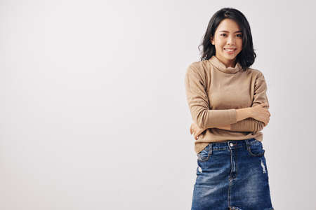 Portrait of young beautiful Vietnamese woman in denim skirt and camel sweater smiling at camera, isolated on white Stok Fotoğraf