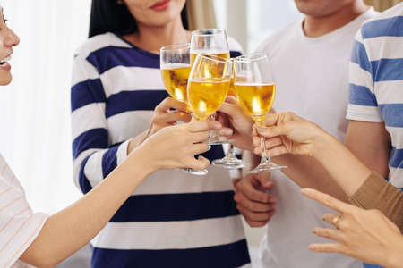 Close-up image of friends clinking glasses of white wine at party