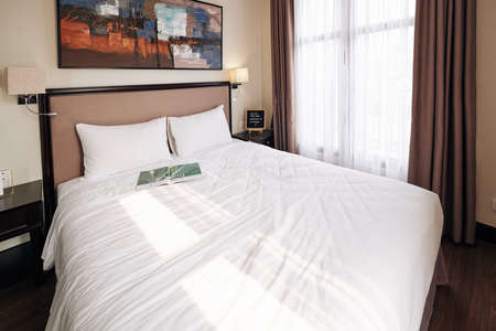 Queen size bed with opened magazine in beautiful suite ready for new guests Stock fotó