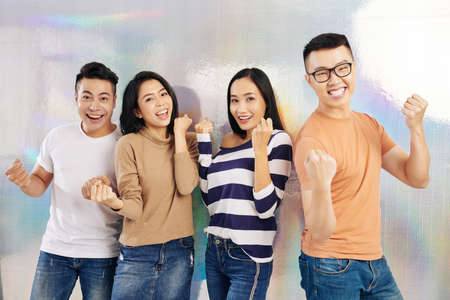 Group of excited happy young Asian people making fist bump when celebrating successful project