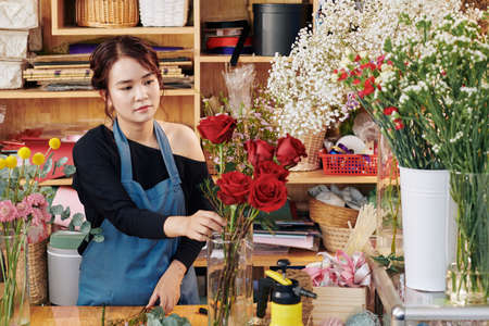 Young pretty Asian florist working at counter and putting fresh flowers into vase Archivio Fotografico - 132759687