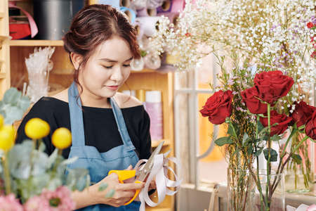 Pretty young Asian florist cutting ribbon to decorate bouquet of flowers Archivio Fotografico - 132759690