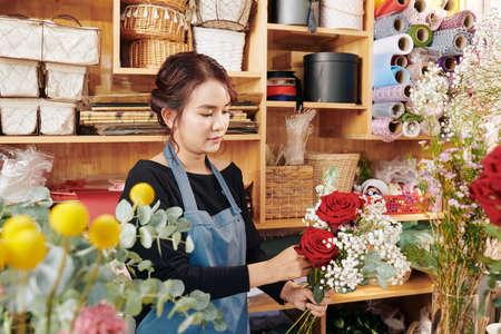 Young Asian florist making beautiful bouquet for customer Archivio Fotografico - 132759692