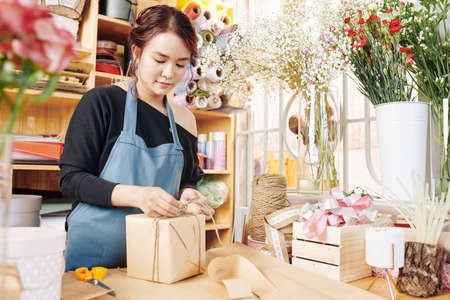 Pretty young Vietnamese woman wrapping presents when working at counter in flower shop Archivio Fotografico - 132759699