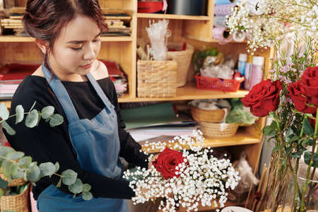 Young Vietnamese woman arranging roses and gypsophila flowers in bouquet Archivio Fotografico - 132759700