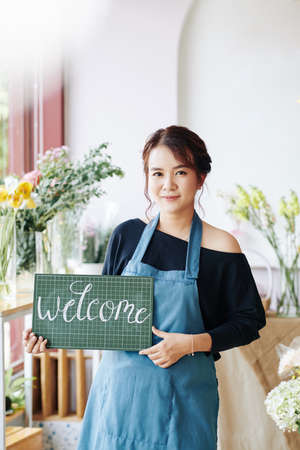 Portrait of young Asian woman in aprons holding welcome signboard and inviting customer to her flower shop Archivio Fotografico - 132759701