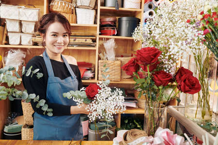 Portrait of pretty creative young florist working in her studio