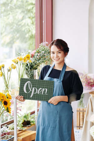 Lovely smiling Vietnamese florist in blue apron holding open sign and looking at camera Archivio Fotografico - 132759706