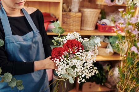 Female florist showing beautiful bouquet with red roses, gypsophila and eucalyptus Archivio Fotografico - 132668555